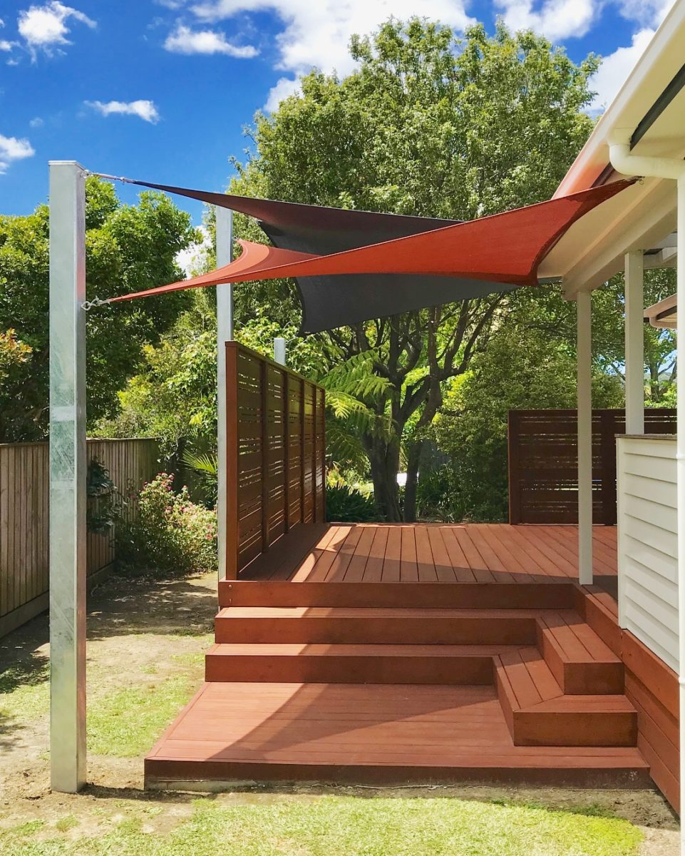 Shade sail over back deck creating a shady seating area
