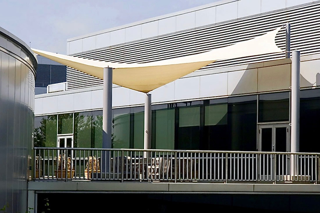 Commercial building with shade sail over outdoor deck area